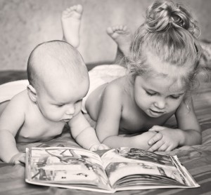 Little brother and sister looking at a book while lying on bed